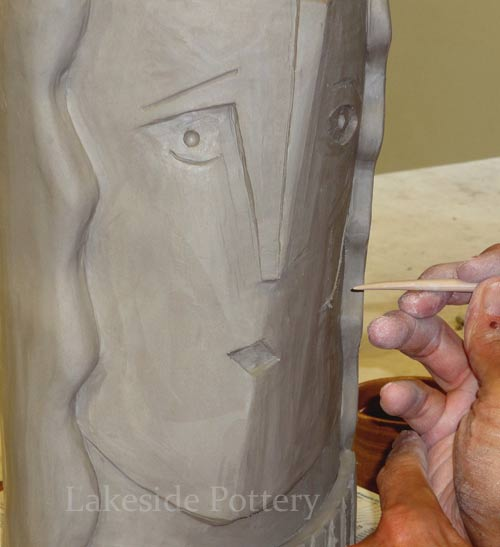 sculpting obstract face on vase