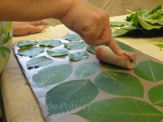 impressing leaves on clay