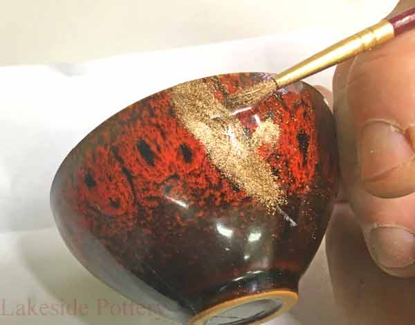 Use very soft brush to apply the gold powder over the lacquer